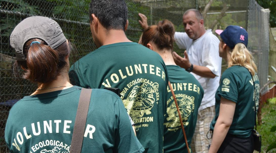 Amazon Rainforest Conservation interns listen to a staff member as he takes them through the various wildlife in the rehabilitation centre in Peru.